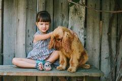 国家女孩坐与她的狗的一条长凳在藤下 木 免版税库存图片