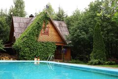 国家有常春藤门面和露天游泳池的村庄房子 库存照片