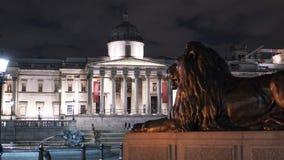 国家肖像馆和狮子在特拉法加广场伦敦在晚上 库存图片