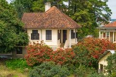 国家舒适甜房子在有铺磁砖的屋顶的一个庭院里 库存图片