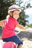 国家(地区)自行车乘驾的小女孩 免版税库存图片