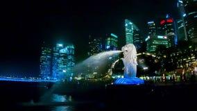 国家-与鱼尾巴的一头狮子的标志 与一个喷泉的一个大雕象在岸在晚上 股票录像