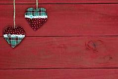 国家织品垂悬从绳索的圣诞节心脏反对古色古香的红色木背景 免版税库存图片