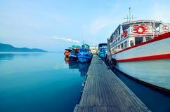 国民,在码头的多彩多姿的游船在日落 小船停泊在泰国,轰隆鲍,张岛 免版税库存照片
