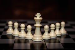 国王在领导前面,管理的典当概念的棋子立场 免版税图库摄影