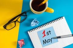 国际劳动节 5月1日天1可以月,在笔记薄的日历在蓝色背景 春天…上升了叶子,自然本底 免版税库存图片