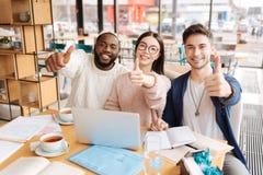 国际学生表现出情感在咖啡馆 免版税图库摄影