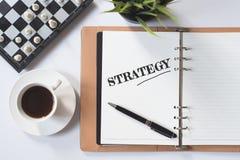 国际象棋棋局、咖啡、绿色植物和笔记本有战略词的在白色舱内甲板位置 免版税图库摄影