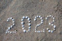 图'2023年'被计划在与壳的沙子上 图库摄影