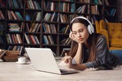 图书馆在家创造性的职业说谎的听的音乐的少妇作家 库存照片