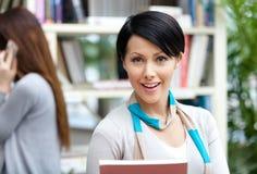 图书馆的少妇学生反对书架 免版税库存图片