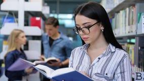 图书馆 在架子附近的微笑的妇女阅读书在大学 股票视频