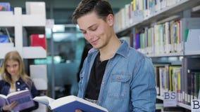图书馆 在架子附近的微笑的男学生阅读书 影视素材