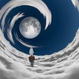 图在漂浮对满月的白色长袍 免版税库存照片