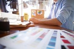 图形设计和颜色样片和笔在书桌上 与工作工具和辅助部件的建筑图画 免版税库存照片