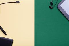 图形输入板和数字式片剂在黄色和绿色背景 库存图片