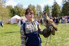 图拉9月, 16 2017年,俄罗斯-历史节日` Kulikovo领域` :有手套的一名妇女拿着在被伸出的手上的一头猫头鹰 免版税库存图片