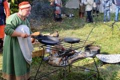 图拉9月, 16 2017年,俄罗斯-节日` Kulikovo领域` :传统衣裳的一名妇女准备在煎锅的食物 库存照片