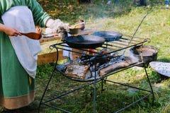 图拉9月, 16 2017年,俄罗斯-节日` Kulikovo领域` :传统衣裳的一名妇女准备在煎锅的食物 图库摄影