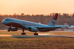 图波列夫214红色翼航空公司着陆在日落 免版税图库摄影