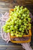 图片从上面的在木箱的绿色葡萄有桃红色布料的 免版税图库摄影