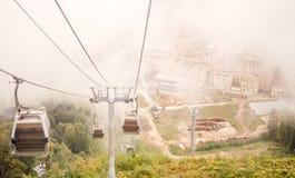 图片的缆索铁路在反对有薄雾的天空背景的山  库存图片