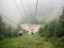 图片的缆索铁路在反对有薄雾的天空背景的山  免版税库存图片