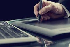图表设计师与数字式片剂笔一起使用 免版税库存图片