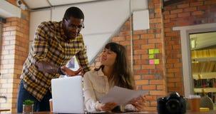 图表设计师谈论在照片在书桌在现代办公室4k 股票录像