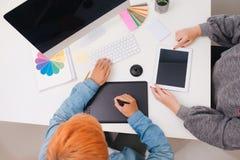 图表设计师谈论在计算机在现代办公室 免版税库存照片