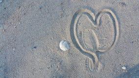 图被践踏的心脏在沙子 免版税库存照片