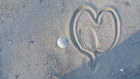 图被践踏的心脏在沙子 免版税库存图片