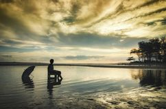 图象剪影坐在日出背景的男孩 库存照片