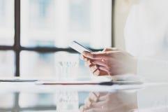 图象女商人与新的起始的项目一起使用在现代coworking的办公室 坐在桌上,拿着智能手机 库存图片