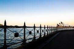 图象显示悉尼港口和从边路的悉尼歌剧院看法在港口桥梁下在暮色时间天空 免版税图库摄影