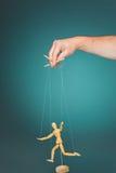图象木偶在操纵傀儡的人的手上 免版税库存图片
