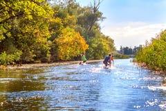 图象男孩在河的桨独木舟 免版税库存图片