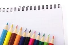 图象的笔记本和五颜六色的铅笔,特写镜头,被隔绝 图库摄影