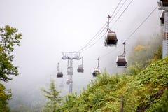 图象的缆索铁路在反对有薄雾的天空背景的山  免版税库存照片