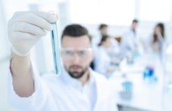 图象被弄脏 拿着有试剂的年轻科学家管 免版税库存图片