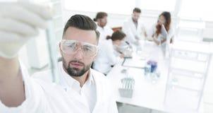 图象被弄脏 拿着有试剂的年轻科学家管 免版税库存照片