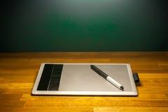 图画片剂和笔在木书桌桌上 免版税库存照片