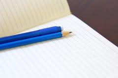 图画铅笔和橡皮擦在一个白色笔记本 免版税库存图片