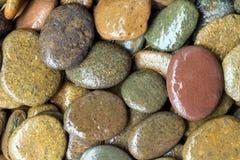 圆弄湿色的石头背景 库存照片