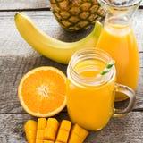 圆滑的人和汁液用热带水果:芒果,香蕉,橙色在木背景的一个玻璃金属螺盖玻璃瓶 库存图片
