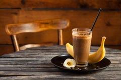 圆滑的人用香蕉和咖啡在土气木桌上 图库摄影