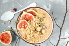 圆滑的人碗用无花果、花生酱和muesli 库存照片