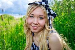 圆点礼服的微笑在春天草甸的年轻美丽的女孩和头饰带在蓝色云彩背景的晴天  库存照片