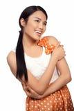 圆点花样的布料的微笑的亚裔女孩穿戴 免版税库存照片