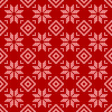 圆点,在一红色backgr的白色雪花的无缝的样式 图库摄影